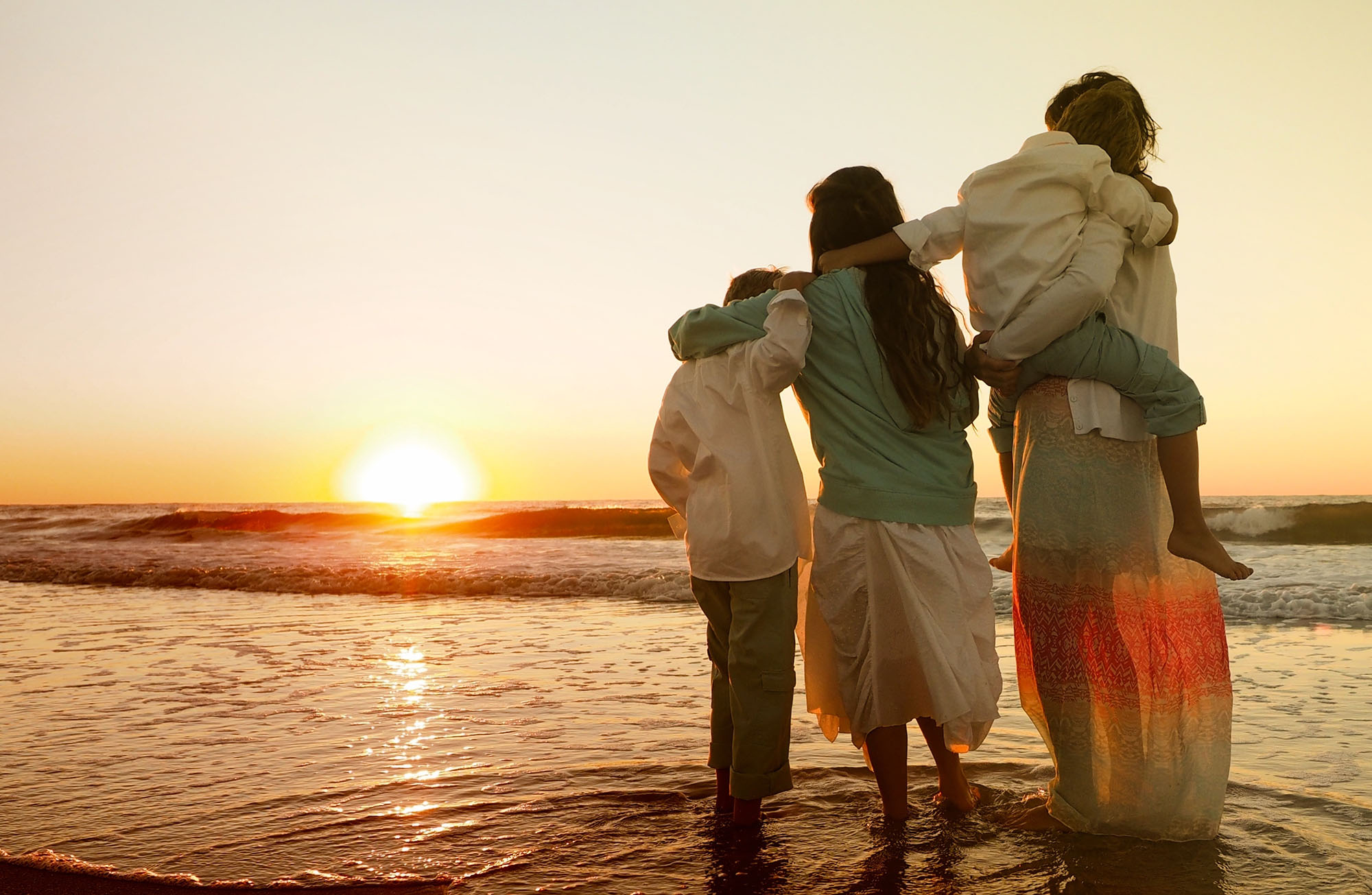 family hugging each other while standing in the beach
