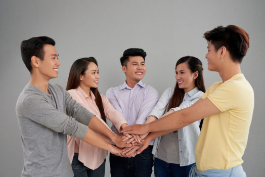 men women posing joining hands together