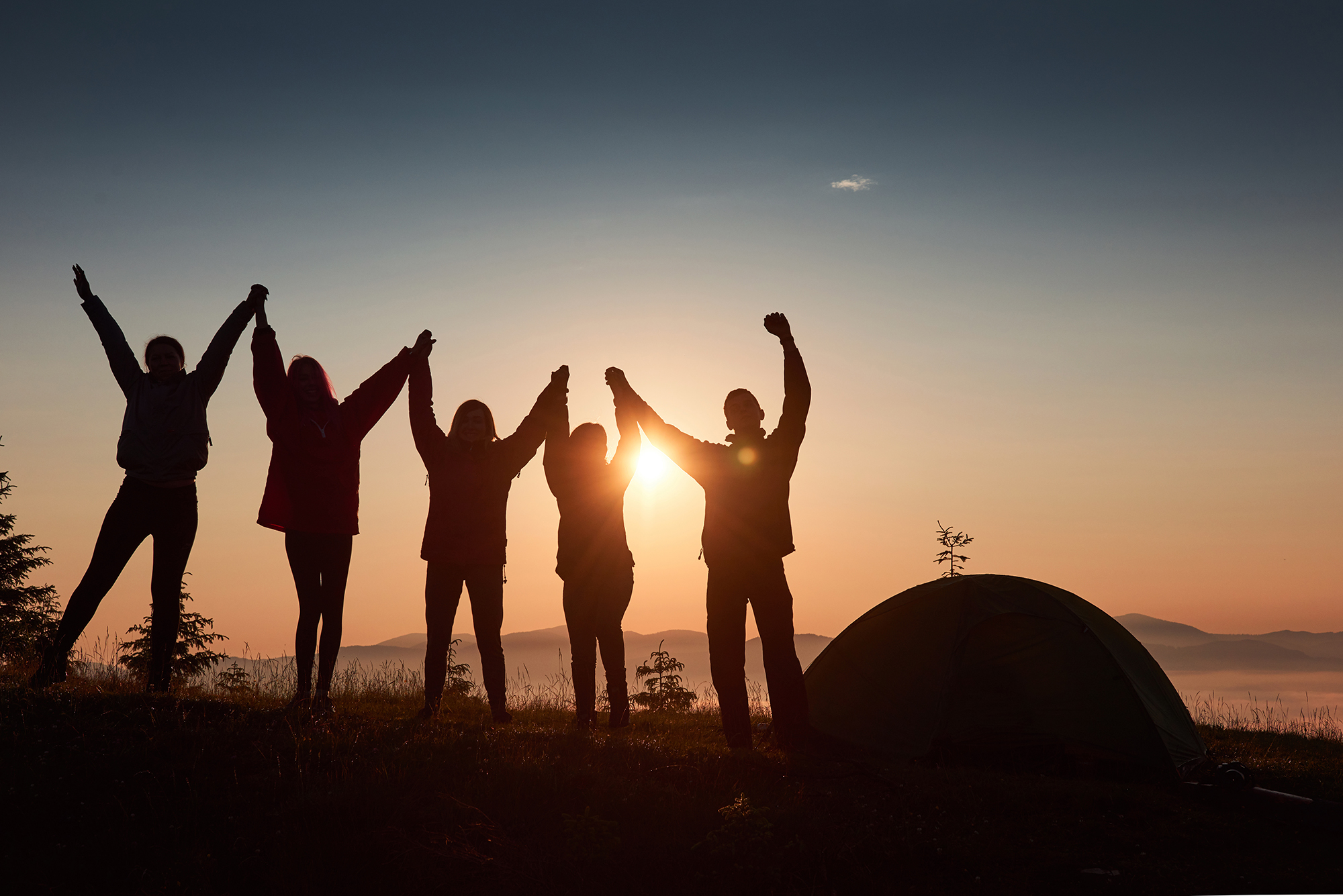 silhouette of group of people having fun near tent during sunset 2