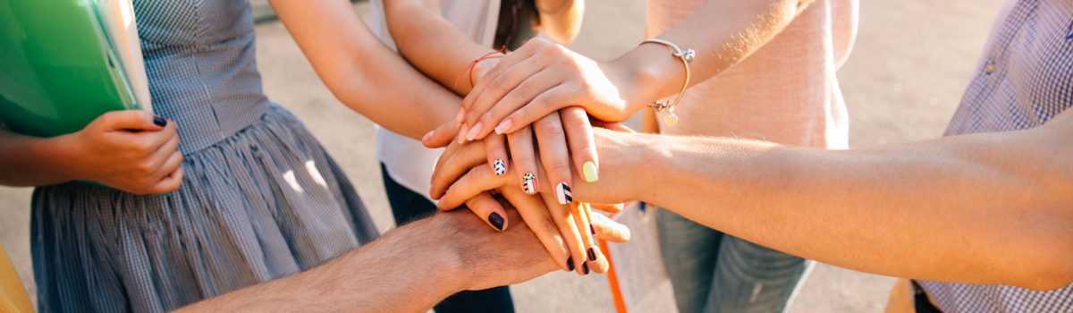 students together stacked hands close-up