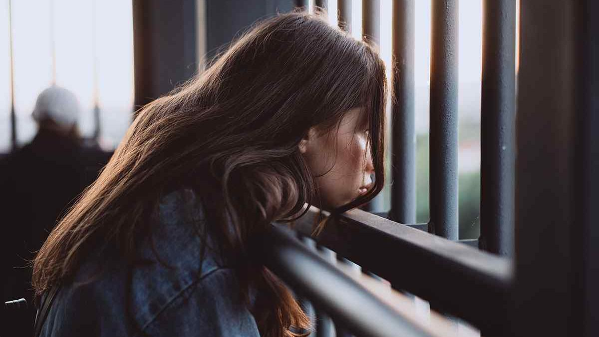 girl looking outside at iron fence