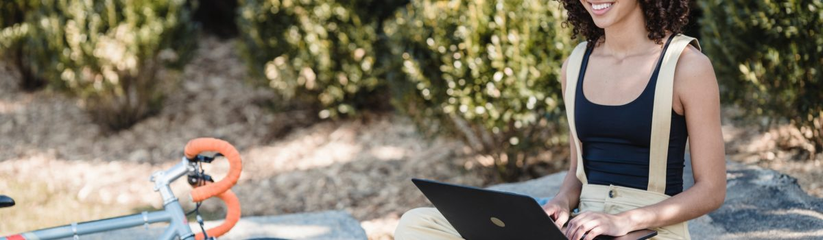 cheerful female using laptop outdoors